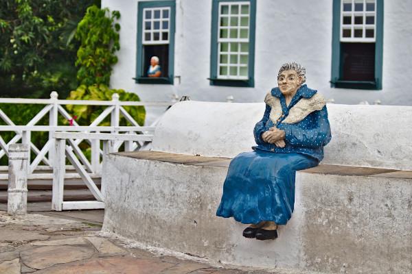 A estátua da poeta encontra-se às margens do Rio Vermelho. Ao fundo há parte da fachada de sua velha casa, hoje Museu Casa de Cora Coralina. [1]
