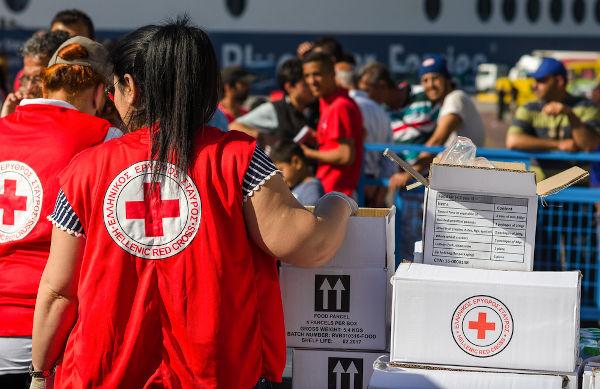 Membros da Cruz Vermelha Grega atuando em benefício de refugiados sírios que chegavam ao país em 2016.[2]