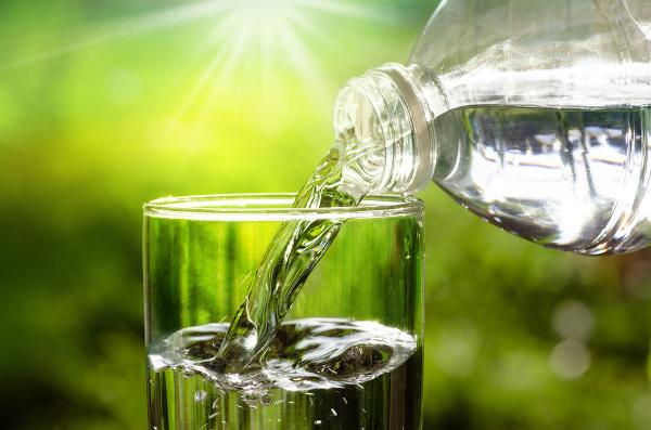 Água em estado líquido sendo despejada em um copo, aderindo ao formato do recipiente.
