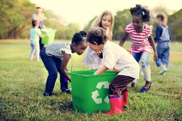 Grupo de crianças recolhendo materiais recicláveis e colocando em uma lixeira com o símbolo de reciclável.