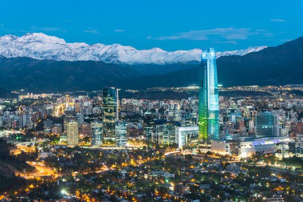 Foto aérea da cidade de Santiago, capital do Chile, repleta de edifícios e com uma cadeia de montanhas ao fundo.