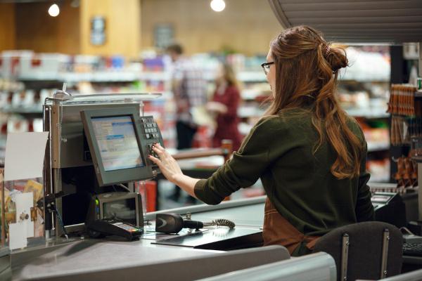 Mulher trabalhando em um caixa de supermercado.