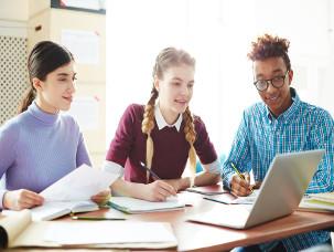Estudantes com notebook e anotações