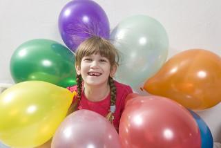 Os cabelos da menina estão eletrizados e são atraídos pelos balões – essa é uma evidência da natureza elétrica da matéria