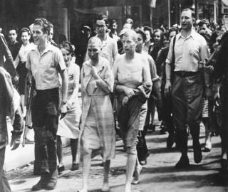 Mulheres acusadas de colaboração horizontal com soldados nazistas sendo escrachadas publicamente em Paris, França, em 1944