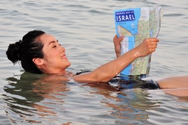 Mulher divertindo-se nas águas do Mar Morto, nas quais não é possível afundar. ¹