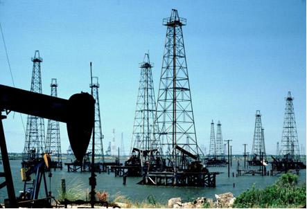 """Uso de """"cavalo de pau"""" (à esquerda) e torres de perfuração (ao fundo) para exploração do petróleo"""