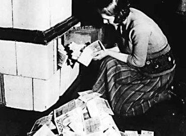 A crise da economia alemã: uma mulher usa dinheiro para aquecer sua lareira.