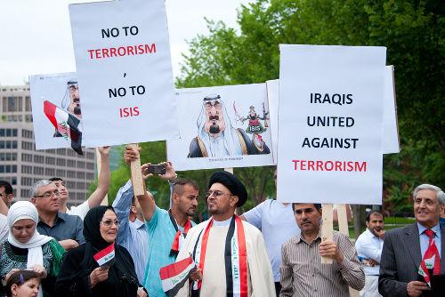 """A placa à esquerda diz: """"Não ao terrorismo, não ao ISIS!"""". A placa à direita diz: """"Iraquianos unidos contra o terrorismo"""" *"""