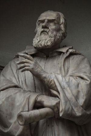 Acima, estátua de Galileu Galilei segurando um modelo de telescópio