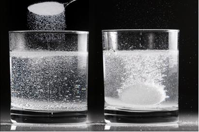 Reação entre antiácido efervescente e água em duas situações diferentes: no primeiro copo, o antiácido está em pó e, no segundo, está em comprimido