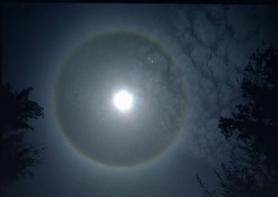 O halo que se forma ao redor da Lua se deve à refração da luz em cristais de gelo presentes na atmosfera.