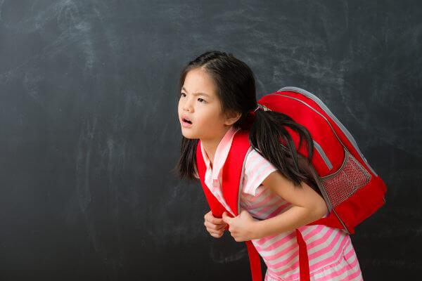 O uso de mochilas pesadas por crianças e adolescentes pode desencadear dores.
