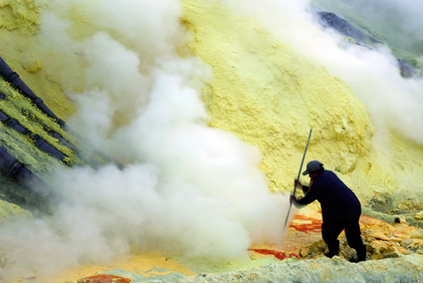 Mineiro de enxofre em cratera do vulcão, com a mínima proteção num ambiente de trabalho perigoso, em 2010, na Indonésia*