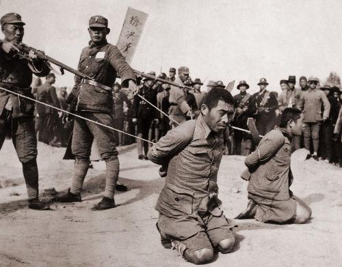 Dois prisioneiros chineses ajoelhados poucos antes de sua execução.