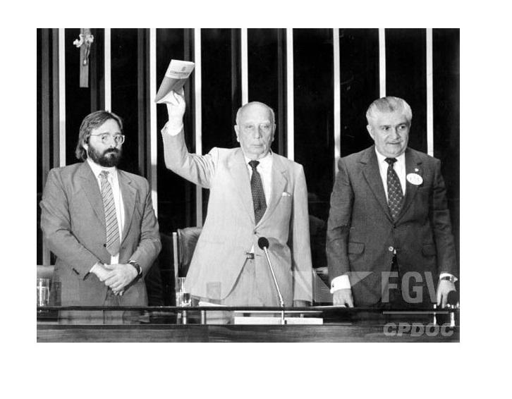Marcelo Cordeiro, Ulysses Guimarães e Mauro Benevides apresentam o modelo da Constituição que foi promulgada em 1988.*