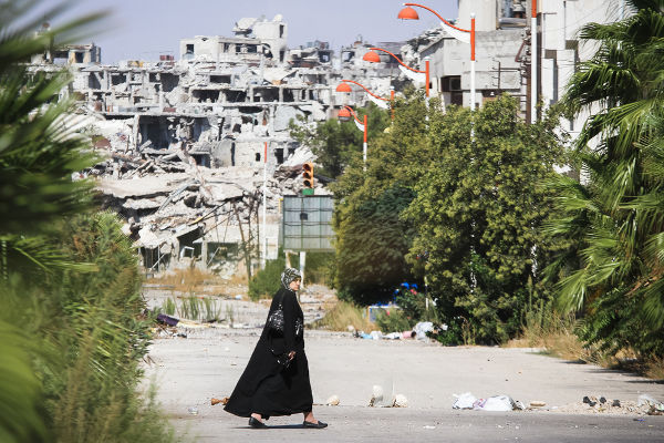 Mulher caminhando pela cidade síria de Homs em setembro de 2013 *