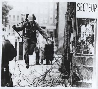 Oficial da Alemanha Oriental saltando os arames após o início da construção do Muro de Berlim *