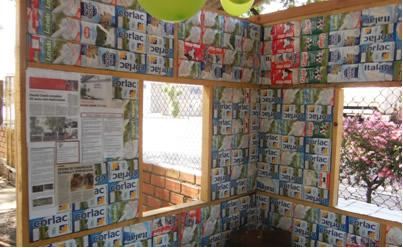 Casa com paredes revestidas com caixas de leite