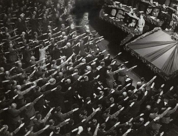 Pessoas saudando Hitler durante reunião nazista. [1]