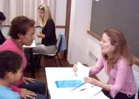 Professora, mãe e aluno em reunião de entrega de boletim