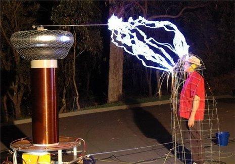 Homem protegido, de uma descarga elétrica, por uma gaiola metálica.