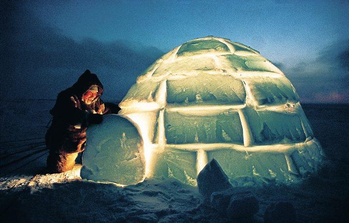 Um esquimó e seu iglu: casa feita de blocos de gelo