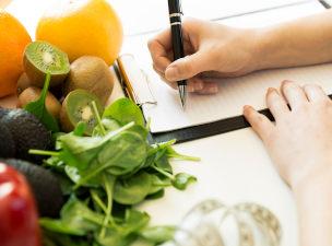 Mão feminina escrevendo em papel ao lado de verduras e frutas
