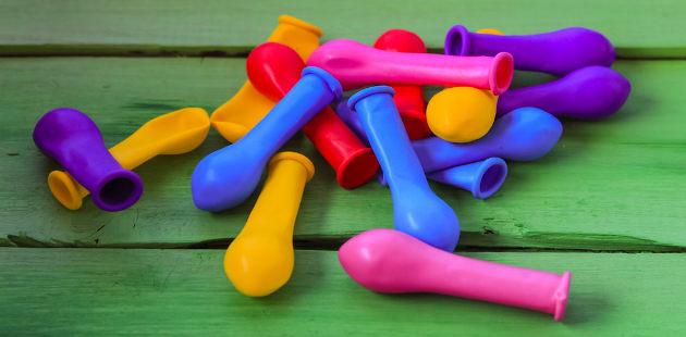 Balões coloridos vazios sobre superfície de madeira
