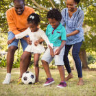 Mãe e pai jogando futebol com os dois filhos