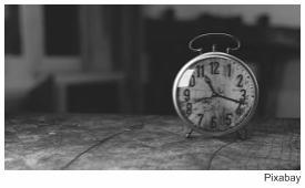 Foto de um relógio despertador, em preto e branco, em enunciado de questão da Unesp 2018