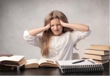Criança com dor de cabeça ao fazer tarefa de casa devido à dificuldade de enxergar