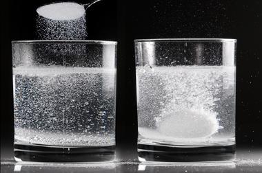 Reação entre antiácido efervescente e água em duas situações diferentes: no primeiro copo, o antiácido está em pó; no segundo, está em comprimido