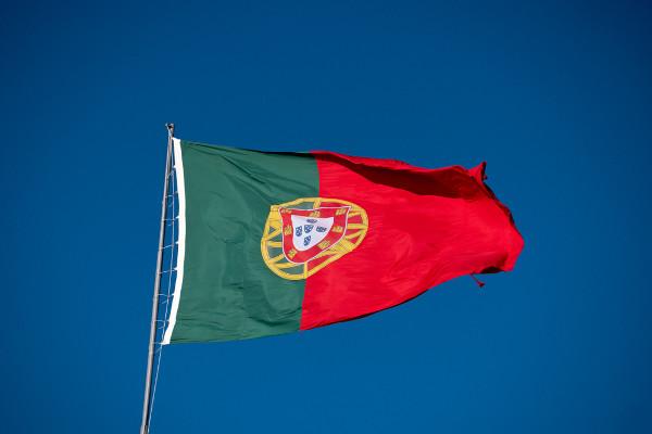 Bandeira de Portugal tremulando em céu azul.