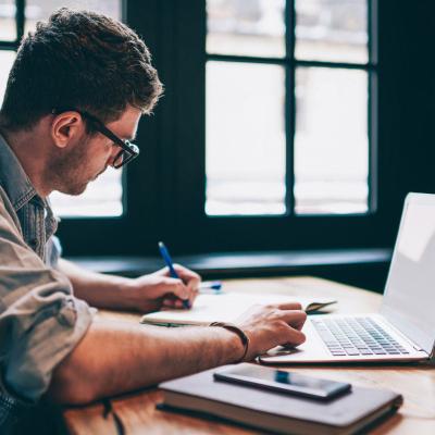 Homem estudando com notebook e caderno