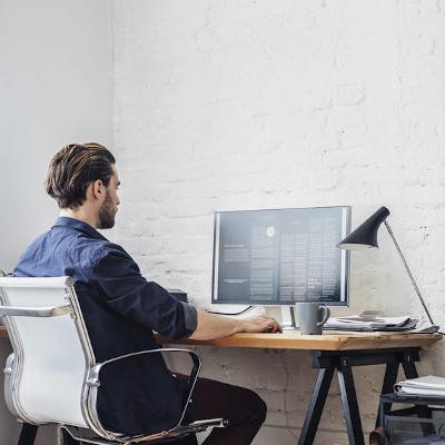 Homem sentado em cadeira de frente para computador