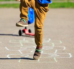 Criança pulando amarelinha desenhada de giz no chão