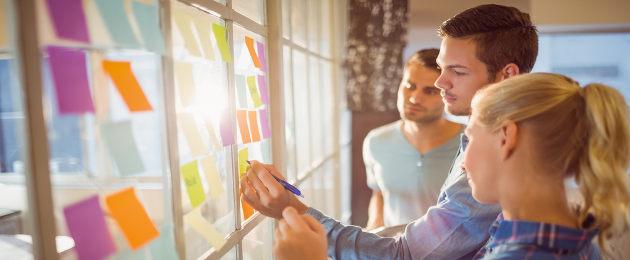 Homens e mulheres jovens escrevendo em post-its coloridos colados em janela