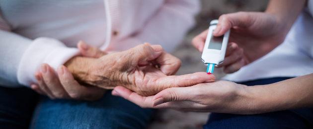 Mulher fazendo teste de glicose em dedo de idosa
