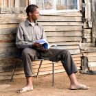 Homem descalço sentado em cadeira de madeira com livro na mão