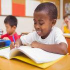 Criança negra escrevendo em caderno